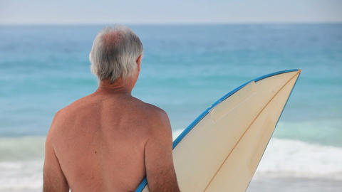 Mature man looking at the ocean with a surfboard Footage