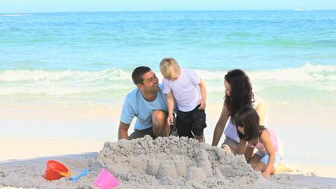Joyful family building a sand castle Footage