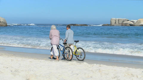 Aged couple walking with bikes Footage