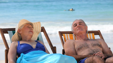 Elderly couple relaxing on beach chairs Footage
