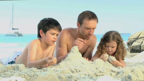 Father and his childs building a sand castle Footage