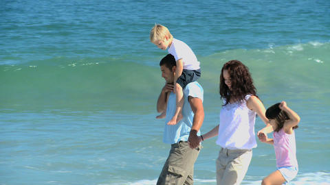 Cute family walking along the sea Footage