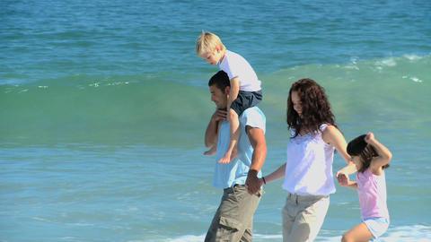 Cute family walking along the sea Footage