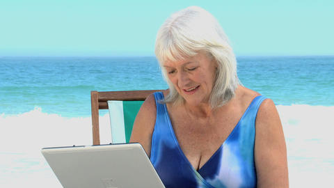 Elderly woman chatting on her laptop Footage