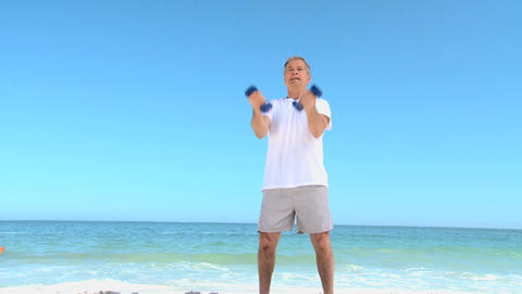 Mature man working his muscles with dumbbells Footage