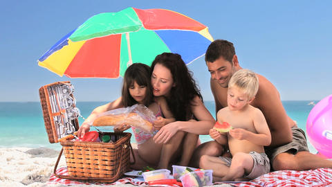 Cute family having a picnic on the beach Footage