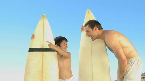 Man and boy with surfboard talking both Footage