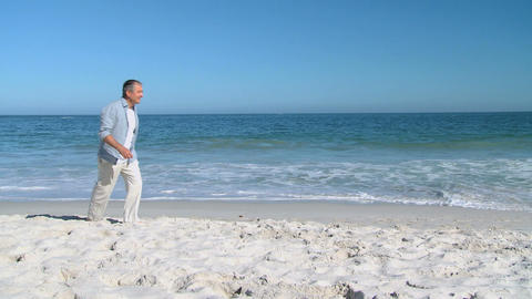 Aged man walking alone on the beach Footage