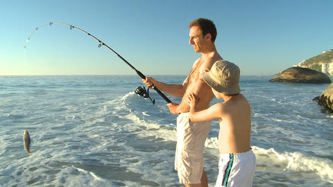 Attractive man fishing with his son Footage