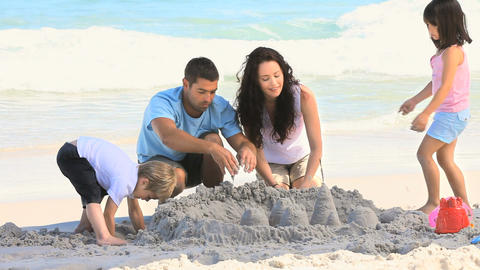 Parents building a sand castle with their children Footage