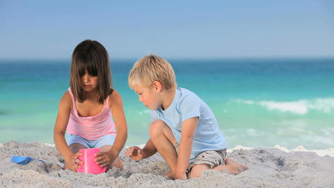 Cute boy building a sand castle with his sister Footage