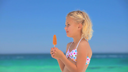 Little blonde girl eating a water ice Footage
