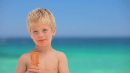 Little smiling boy eating water ice Footage