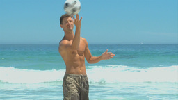 Man coming out of the sea to pick up a soccer ball Footage
