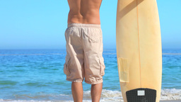 Good looking man with his surfboard looking out to sea Live Action