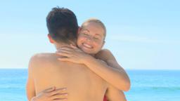Blonde woman hugging her boyfriend on a beach Live Action