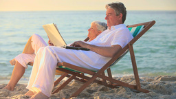 Man using a laptop on a beach while his wife sleep Footage