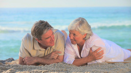 Elderly couple lying on a beach Footage