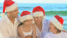Happy family wearing Christmas hats and singing on Footage