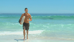Handsome man getting out of the water after surfin Footage