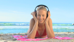 Woman lying on a beach listening to music Footage