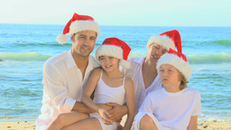 Happy family wearing Christmas hats on a beach Footage