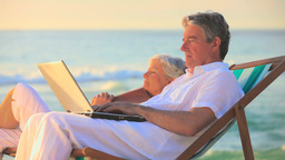 Elderly man using his laptop while his wife is sle Footage