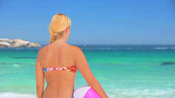 Blonde woman standing looking at the sea Footage