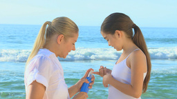 Young girl putting suncream on her mother Footage