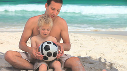 Father and small son sitting on a beach Footage
