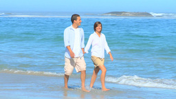 Happy couple walking on a beach Footage