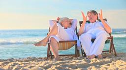 Elderly couple sitting in deckchairs on a beach Footage
