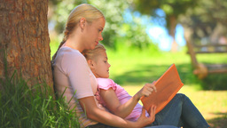 Young woman reading a book with her daughter Footage