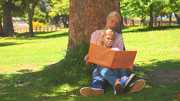 Young girl reading a book with her daughter Footage