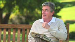 Mature man reading a newspaper on a bench Footage