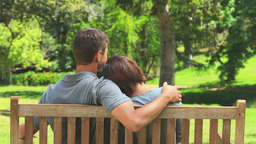 Loving young couple sitting on a bench Footage