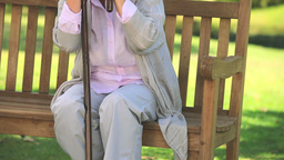 Elderly woman thinking while holding her walking s Footage
