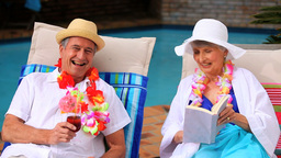 Mature couple with garlands chatting in deckchairs Footage