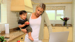 Young mother in kitchen coping with laptop phone a Footage
