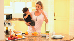 Mother busy in kitchen holding baby while father l Footage