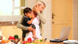 Woman in kitchen coping with baby and laptop and p Footage