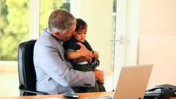 Man in office coping with baby and laptop Footage