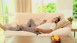 Man lying on sofa enjoying music with headphones Footage