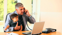 Man holding baby and answering phone at desk Footage