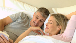 Couple in bed sharing a book and laughing Footage