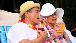 Mature couple with garlands enjoying cocktails Footage