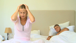 Young woman on bed with headache while husband sleeps Footage