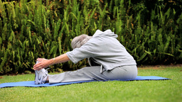 Mature woman doing stretching exercises on lawn Footage