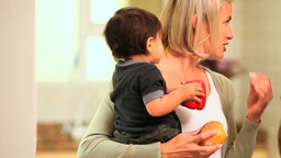 Baby in mothers arms holding a red pepper and eati Footage