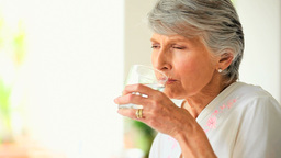 Mature woman sipping a glass of water Footage